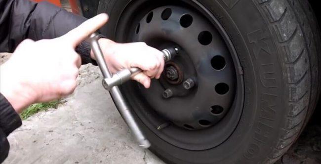 Откручивание креплений вывешенного колеса