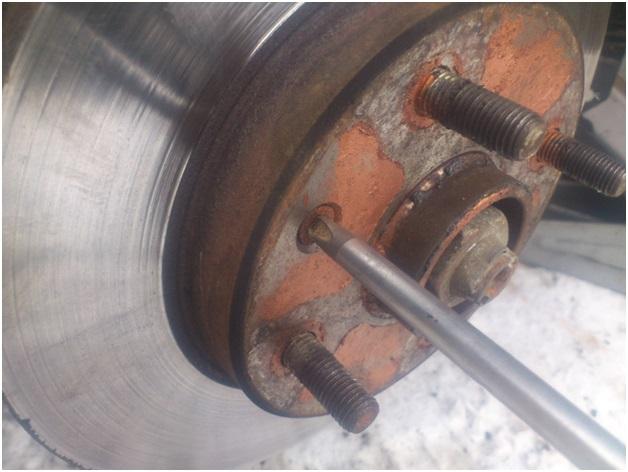 Отворачивание винта, который придерживает тормозной диск