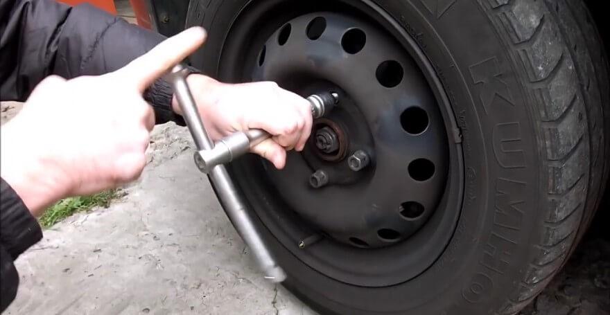 Откручивание креплений колеса баллонным ключом