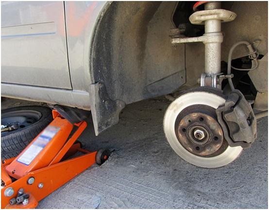 Поддомкраченная Приора с демонтированным колесом