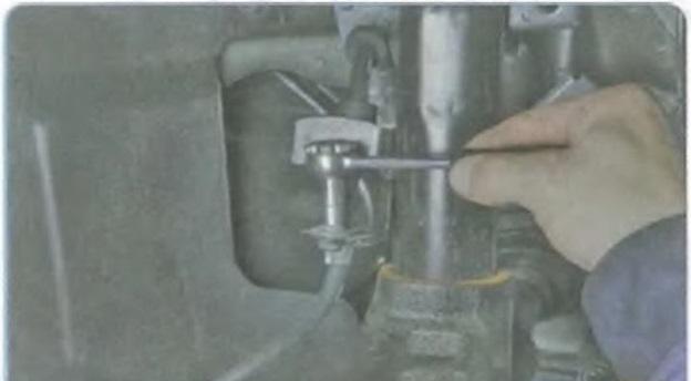 Отворачивание болта крепления держателя тормозного шланга